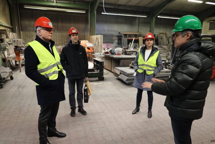 Thomas Zawalski, Schutterwalds Bürgermeister Martin Holschuh und Sandra Detzer stehen bei Uhl in einer Lagerhalle im Gespräch mit Florian Buchta.
