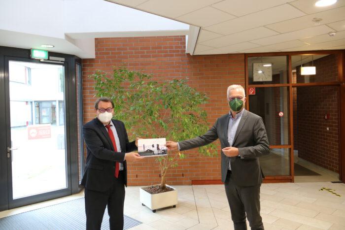 Prof. Dr. Joachim Beck überreicht Thomas Zawalski eine Broschüre der Hochschule Kehl.