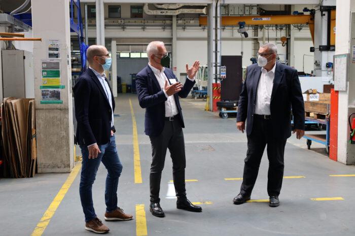 Thomas Zawalski in einer Werkhalle im Gespräch mit den Geschäftsführern Holger Wössner und Uwe Meißner.