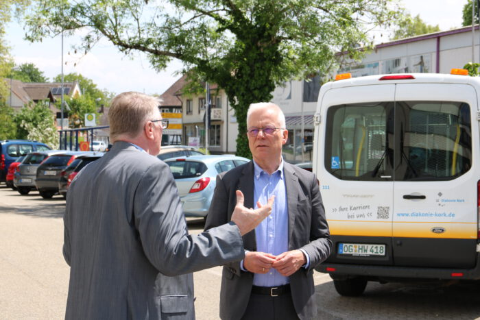 Thomas Zawalski im Gespräch mit Frank Stefan vor einem Fahrzeug der Diakonie.