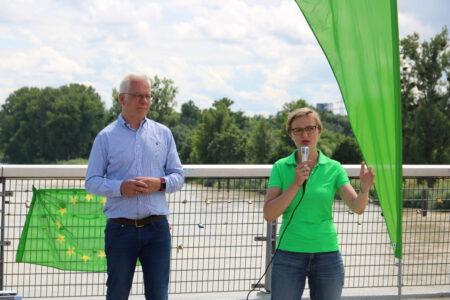Franziska Brantner und Thomas Zawalski stehen vor Fahnen der Grünen auf der Passerelle zwischen Kehl und Straßburg.